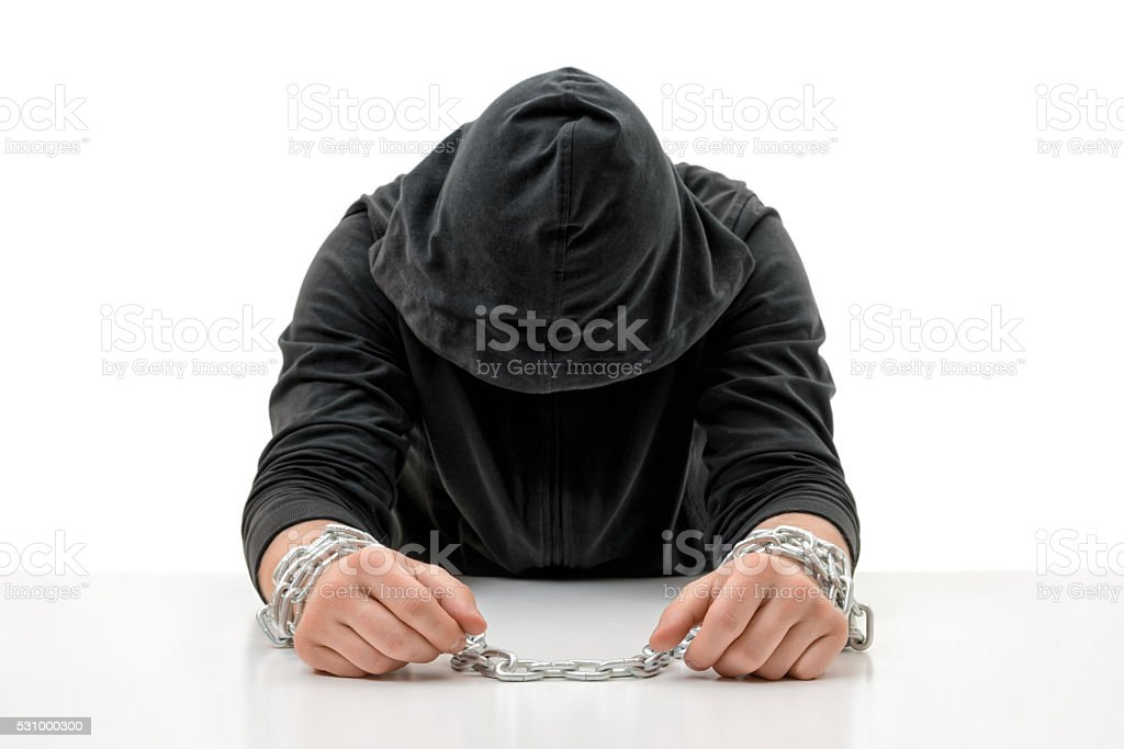 Man with hands in chains is sitting head bowed stock photo