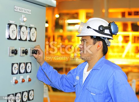 istock Man with hard hat on turning knob 146872638