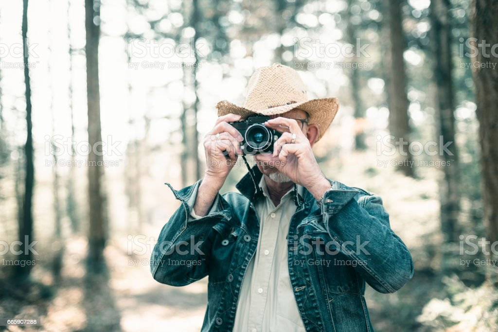 Man with hat and jeans jacket taking picture in forest. foto stock royalty-free