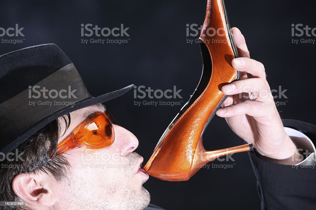Man with hat drinking out of orange high heels stock photo