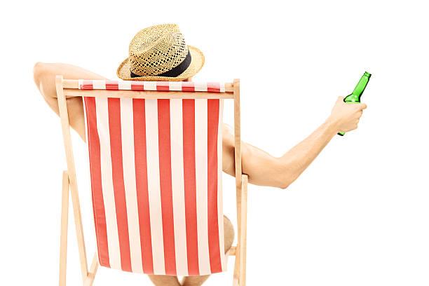 Hombre con sombrero sentada en una silla y una cerveza de retención - foto de stock