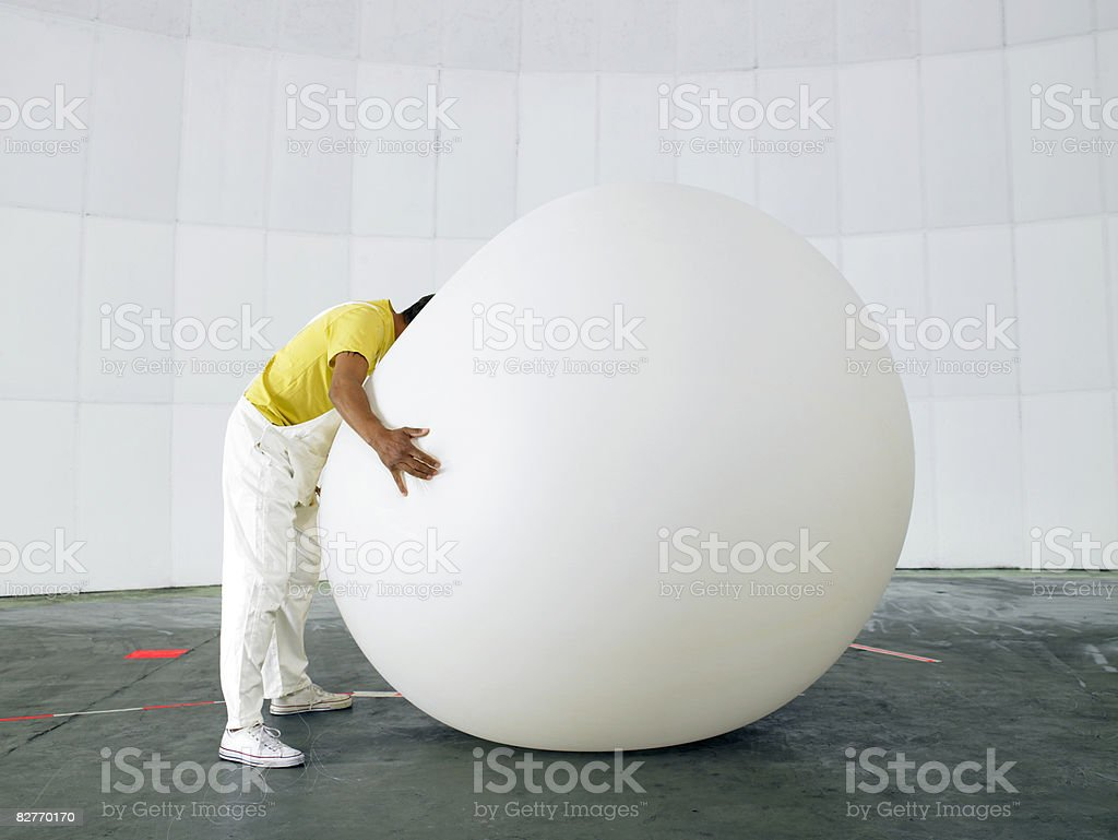 Man with head buried in huge weather balloon royalty free stockfoto
