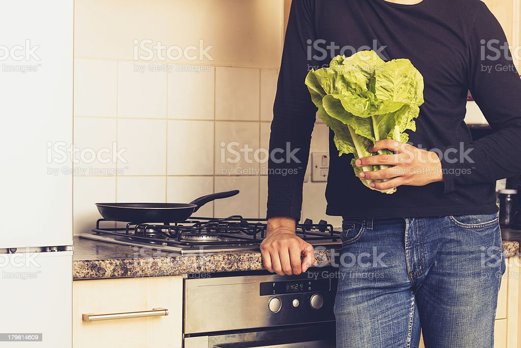 Man with head of lettuce in kitchen royalty-free stock photo