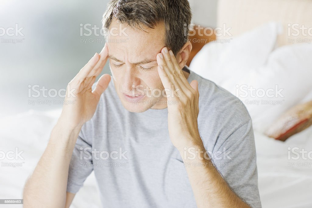 Man with headache rubbing forehead royalty-free stock photo