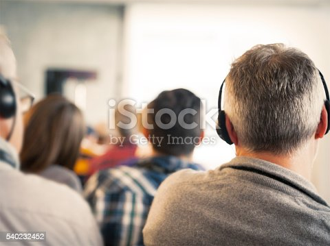 614852062 istock photo Man with headphones and audience at a seminar 540232452