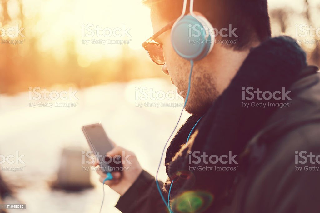 Man with headphones texting on smartphone stock photo
