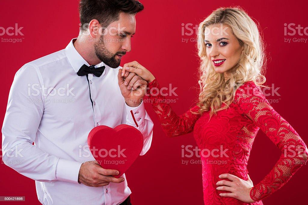 Man with heartshape box holding woman's hand stock photo