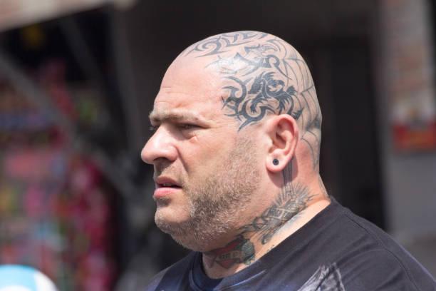 Mann mit stark tätowiertem Kopf – Foto
