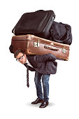 A man is straining under a heavy load of luggage. The seize of luggage is comically large.