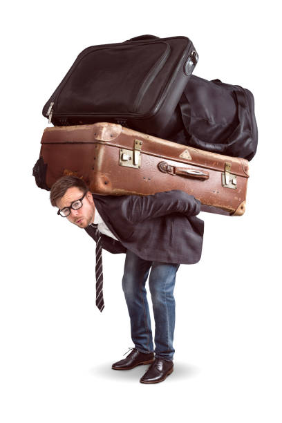 Man with heavy baggage A man is straining under a heavy load of luggage. The seize of luggage is comically large. carrying stock pictures, royalty-free photos & images