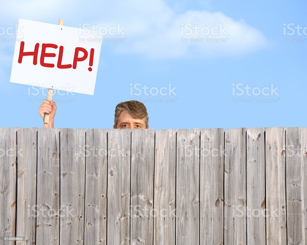 Man with HELP sign looking over wood privacy fence stock photo