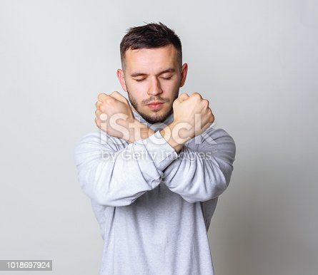 Man with his arms in an X. The handsome in white turtleneck shirt crossed his hands on grey background copy space