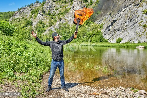 A man with his arms outstretched holds the neck of a burning acoustic guitar against the background of a mountain river on a sunny summer day. Incendiary rock