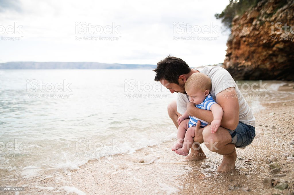 Man with his baby son at the beach having fun. stock photo