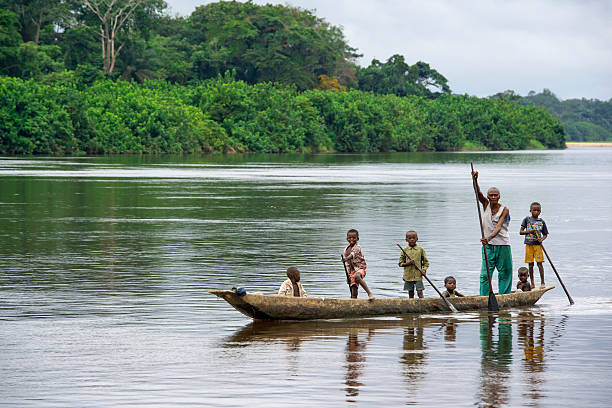 man with his children in a pirogue on congo river - democratic republic of the congo stock photos and pictures