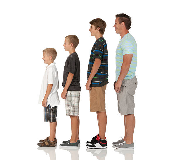 Man with his children standing in a row stock photo