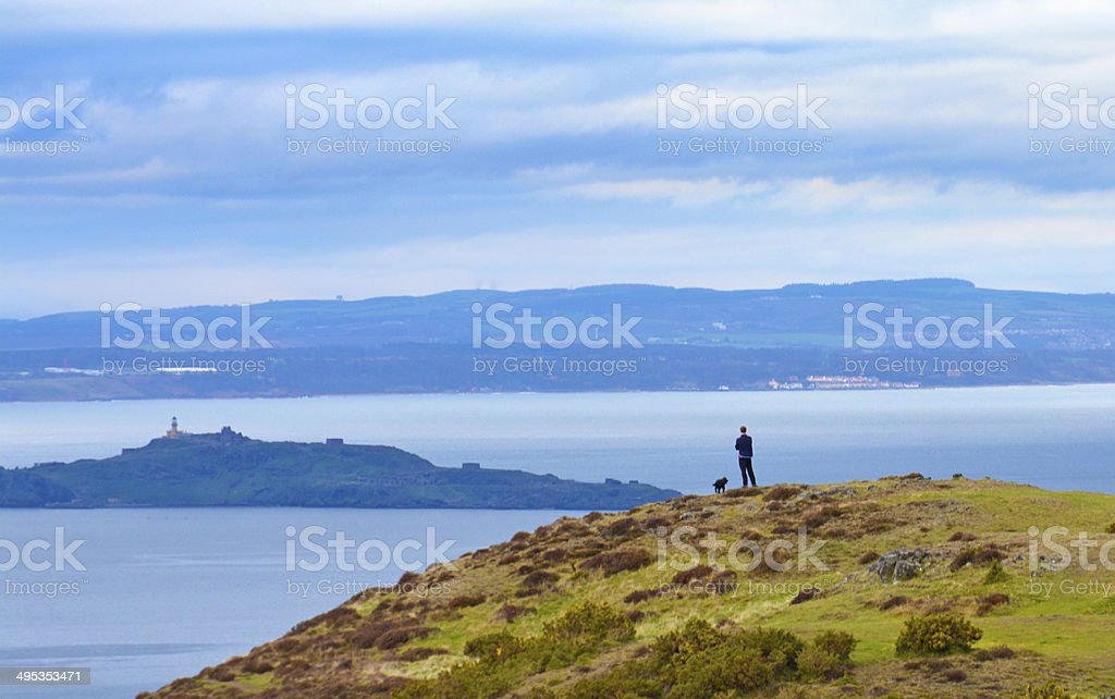 Man with his dog, overlooking a bay with dramatic cloudscape stock photo