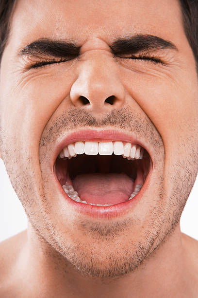 Man with his eyes closed screaming loudly Closeup of young man screaming with eyes closed on white background mouth open stock pictures, royalty-free photos & images