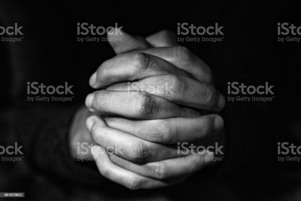 man with his hands clasped, in black and white stock photo