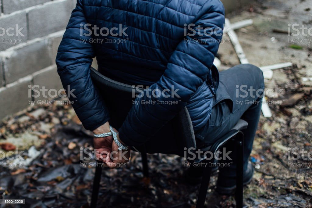 Un hombre con las manos atadas en la espalda sentado en una silla - foto de stock