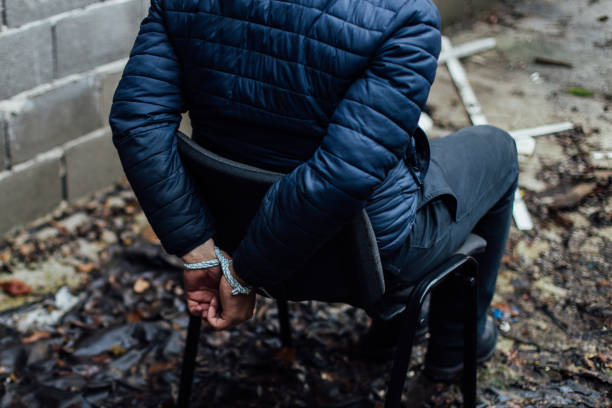 A man with his hands tied on his back sitting on a chair stock photo