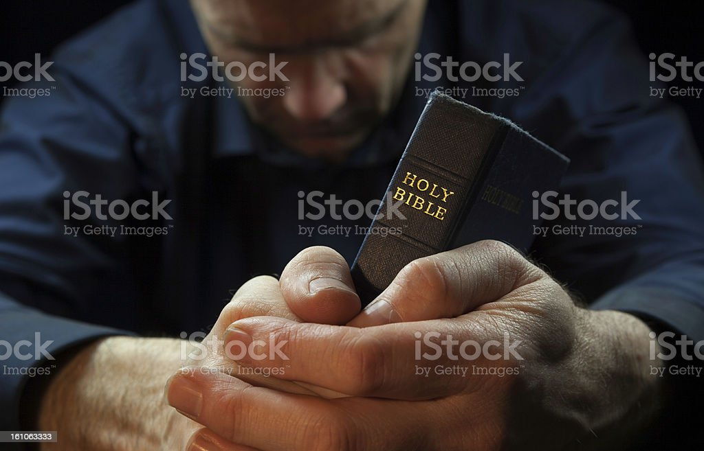 A man with his head bowed and holding a holy bible in prayer stock photo