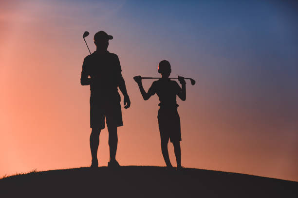 man with his son golfers silhouette stock photo