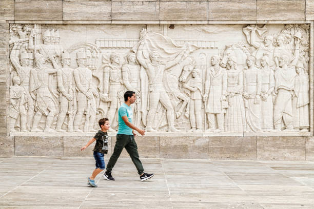 Man with his son walk past the engraving on a wall at the National Flag Monument stock photo