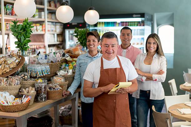 man with his team working at the supermarket - einzelhandelsarbeiter stock-fotos und bilder