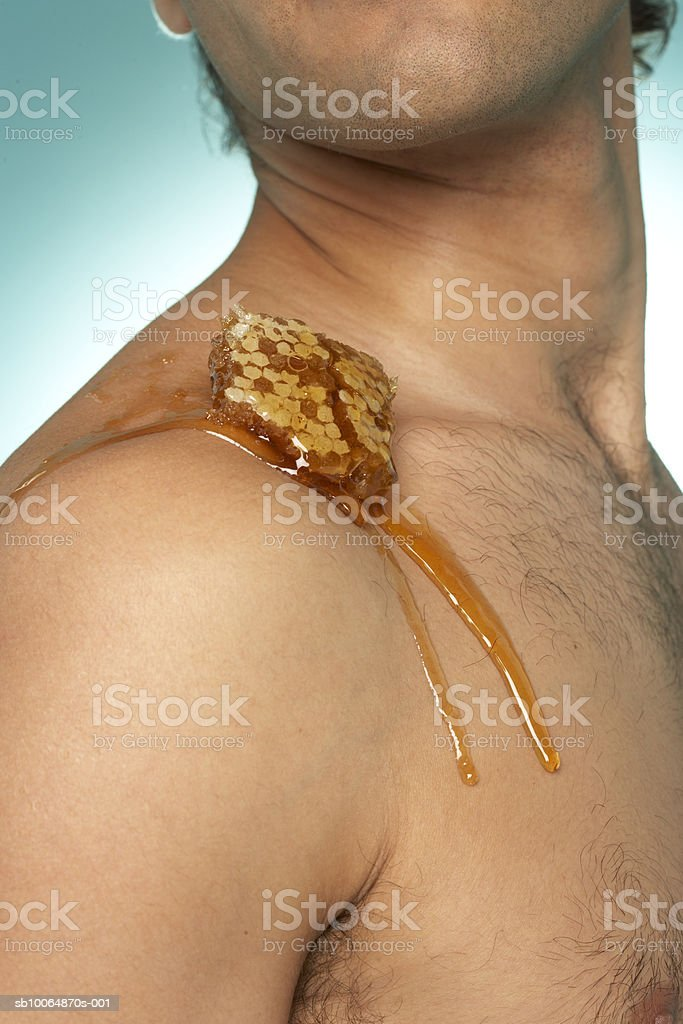 Man with honey comb on shoulder, mid section Lizenzfreies stock-foto