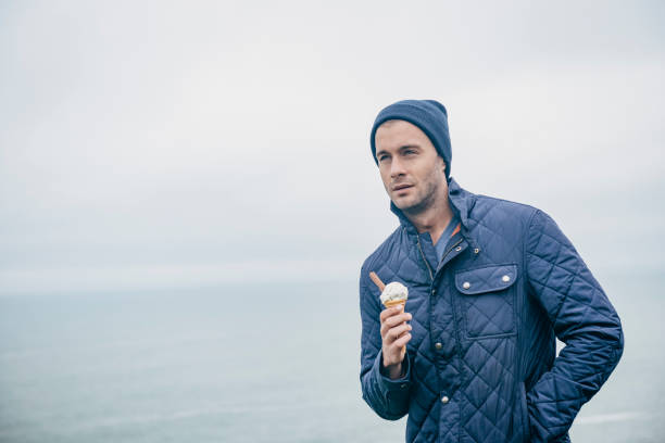 man with ice cream at the cornish coast, newquay, autumn. - ice cream cone stock photos and pictures