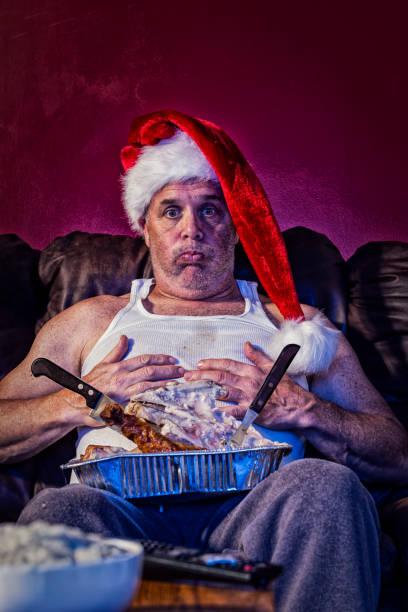 ein mann mit verdauungsstörungen von einem übrig gebliebenen türkei abendessen mit karkasse in seinem schoß hielt seinen bauch tragen einer weihnachtsmütze - trainingshose stock-fotos und bilder