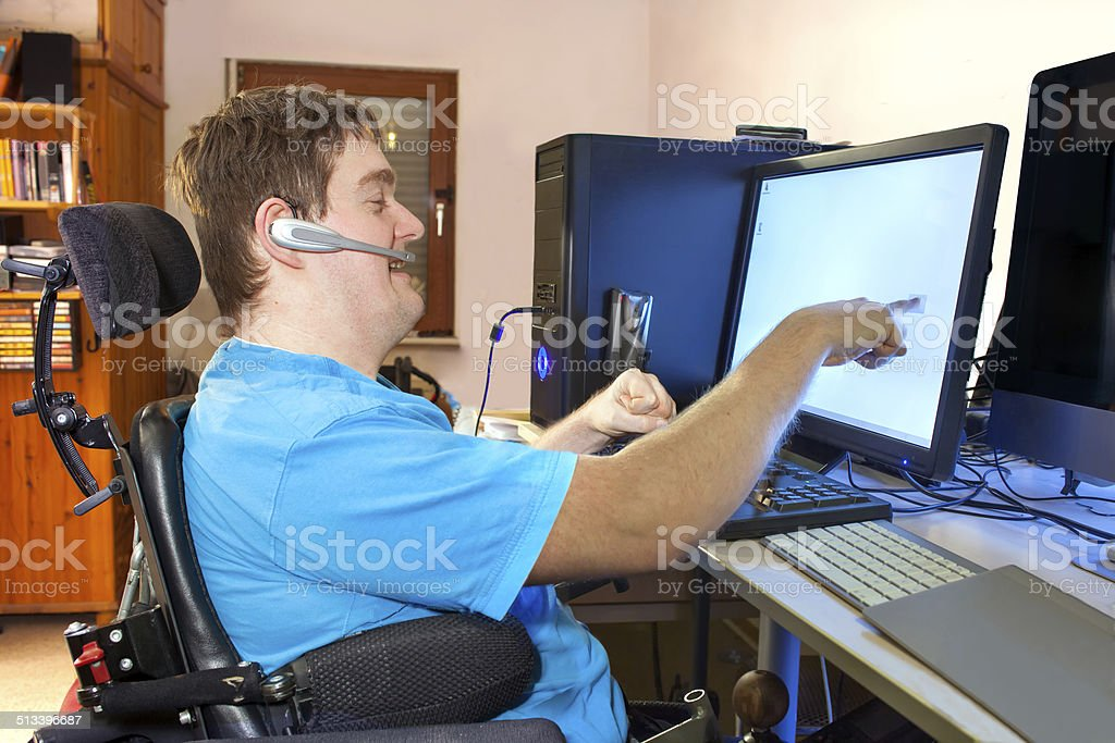 Man with infantile cerebral palsy using a computer. Spastic young man with infantile cerebral palsy caused by a complicated birth sitting in a multifunctional wheelchair, using a computer with a wireless headset, reaching out to touch the touch screen. Adult Stock Photo