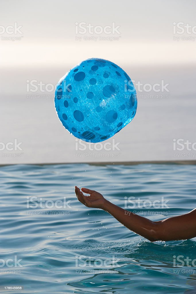 Man with inflatable ball in pool royalty-free stock photo