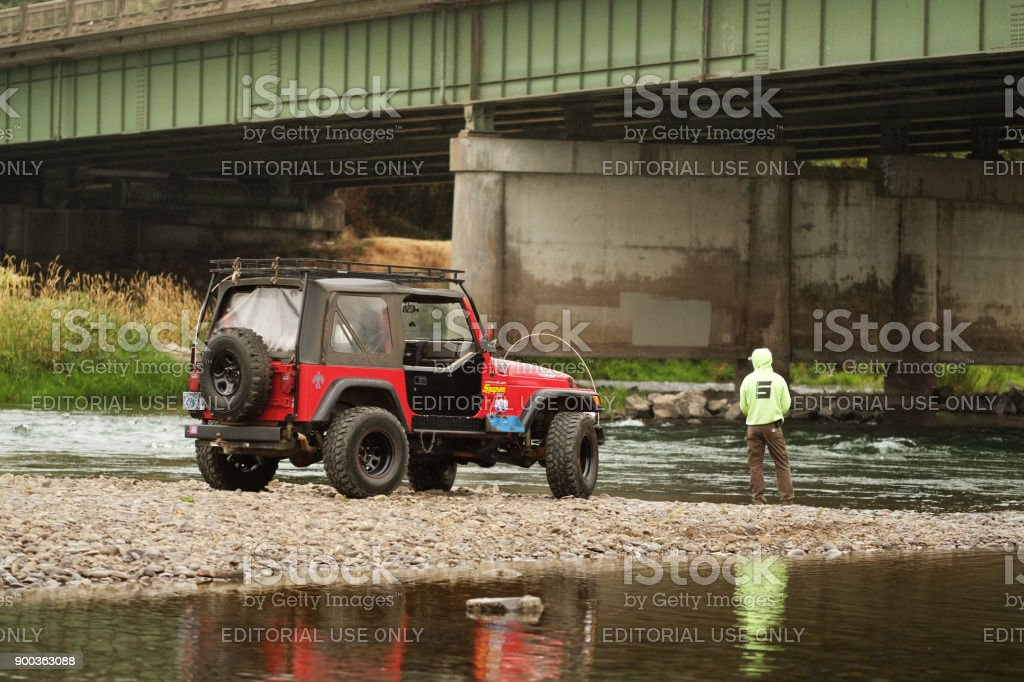 Man with Jeep Fishing from River Bank stock photo