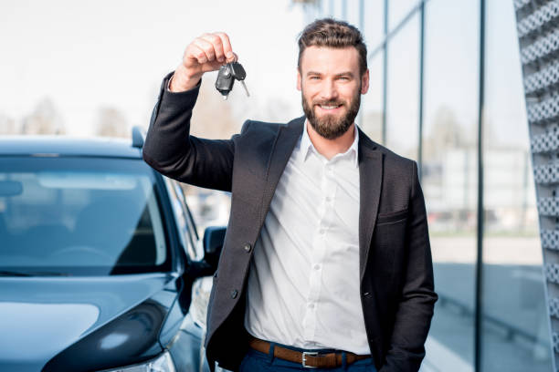 Man with keys near the car Happy buyer holding keys near the car in front of the modern avtosalon building car key stock pictures, royalty-free photos & images