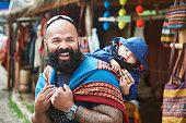 Man with kid in Peru market having fun with alpaca clothes
