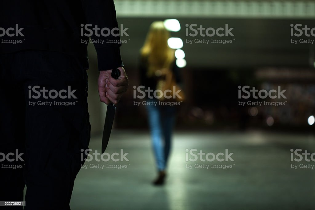 Man with knife following woman stock photo