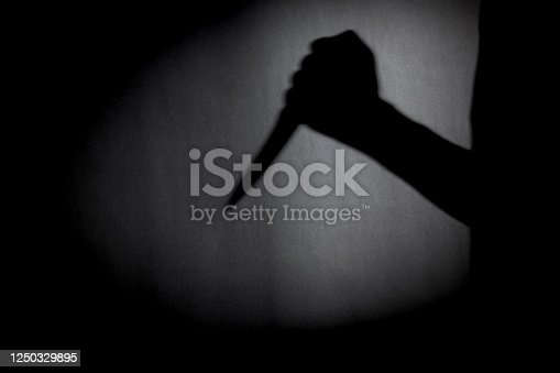 man with knife silhouette over dark wall. black and white photo can be used for illustrating horror and violence attack. crime concept. simple. selective focus. blurred.