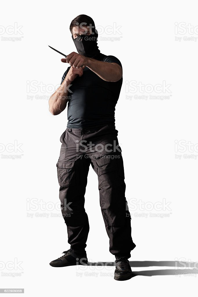 Man with knife standing in prepared position isolated stock photo