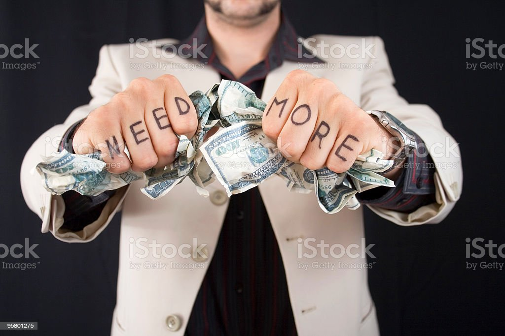 Man with knuckle tattoos holding fistfuls of money royalty-free stock photo