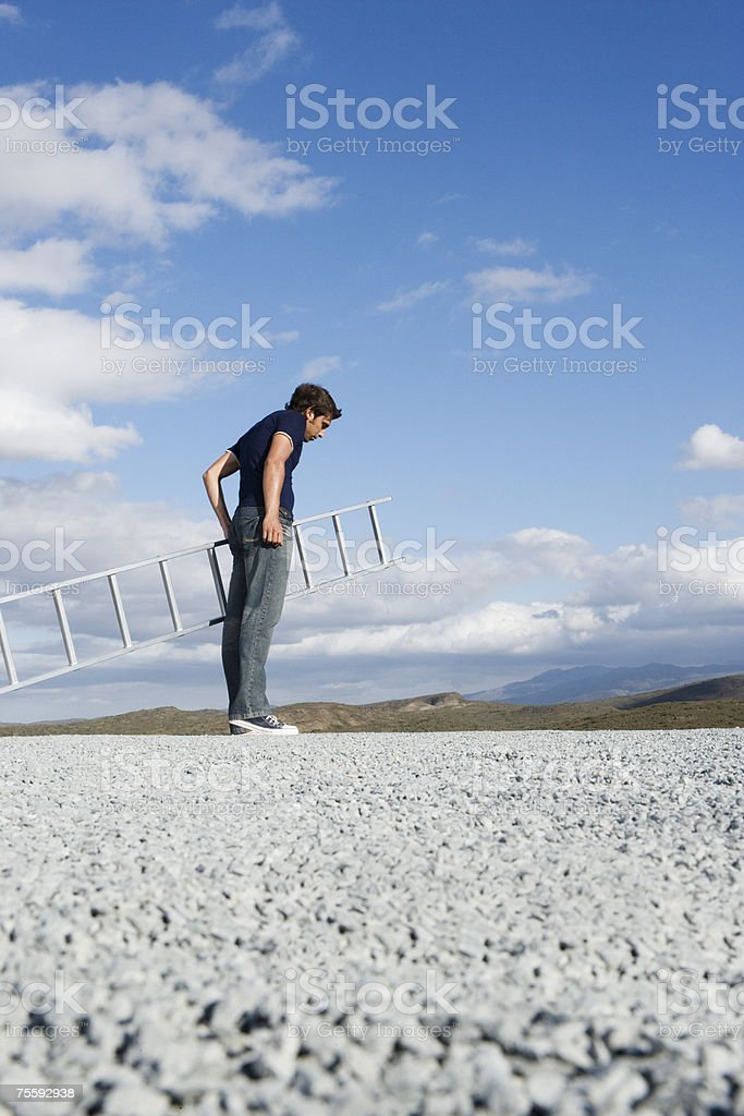 Man with ladder outdoors looking down royalty-free stock photo