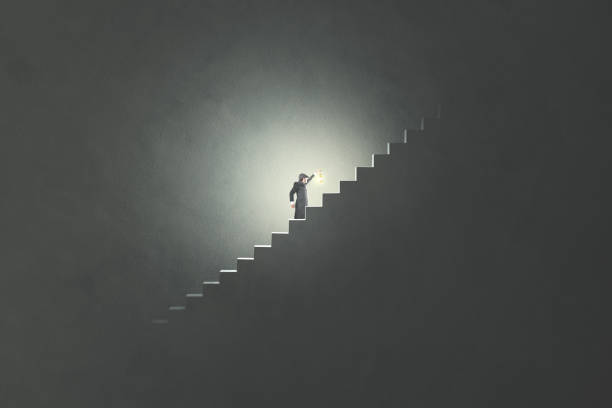 man with lamp rising stairs in the darkness stock photo