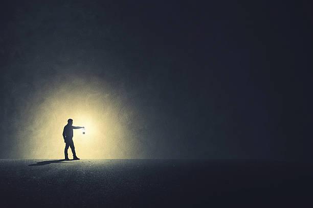 Man with lamp walking illuminating his path stock photo