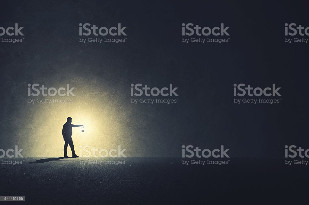Man with lamp walking illuminating his path stock photo