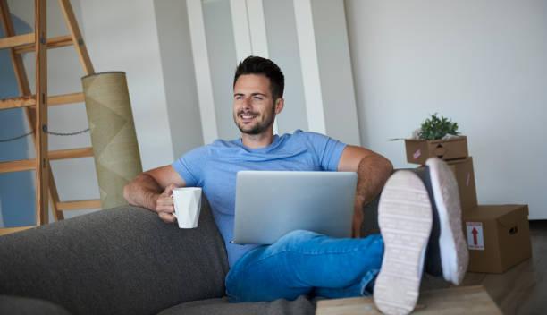 homem com portátil e café que têm a ruptura da casa movente - vida de estudante - fotografias e filmes do acervo