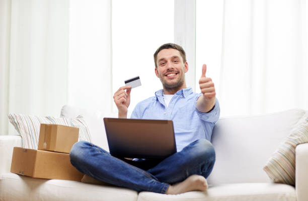 man with laptop and credit card showing thumbs up stock photo