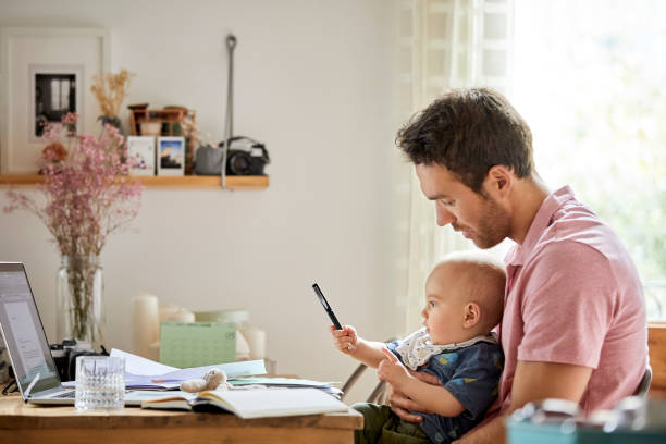 hombre con laptop y papeles mirar hijo juguetón - financial planning fotografías e imágenes de stock