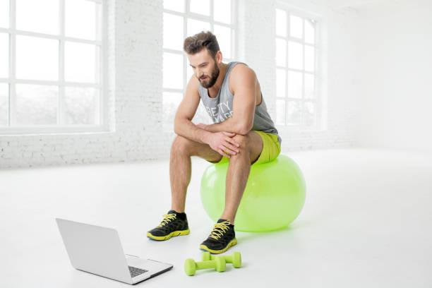 Mann mit Laptop im Fitnessstudio – Foto