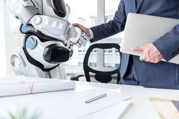 Man with laptop is shaking hands with android stock photo